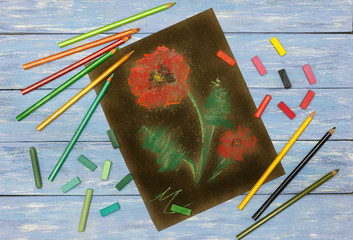sketch with pastels on paper (a red poppy on a black background), pastel chalks and pencils on a blue background in rustic style