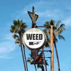 aged and worn vintage photo of weed sign with palm trees