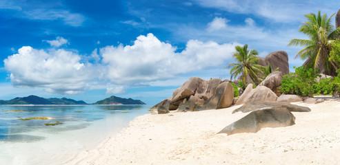 Tropical beach at Seychelles on La Digue island and Praslin island on the horizon. Panoramic image.
