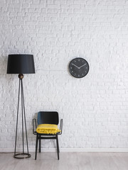 black lamp, chair and clock on the brick wall interior concept