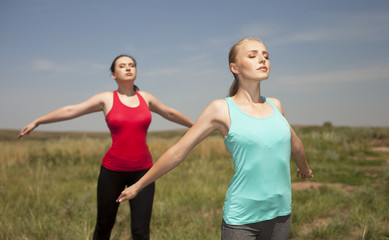 Two young women doing yoga outdoors on blue sky background posin