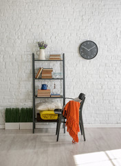 black bookshelf with black chair and black clock with white brick wall interior style
