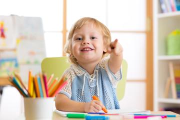 cute child little boy drawing with felt-tip pen in kindergarten classroom