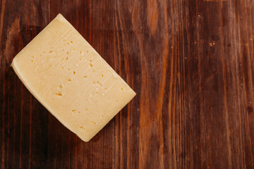 Delicious cheddar cheese on old blue wooden table Top view Copy space