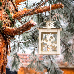 candle stick hanging on a fir branch covered with ice