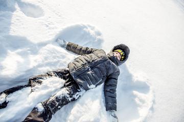 boy lying in the snow.