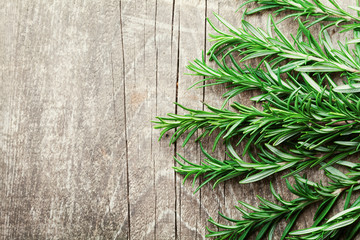 Rosemary plant on wooden rustic table top view, fresh organic herbs with copy space for text.