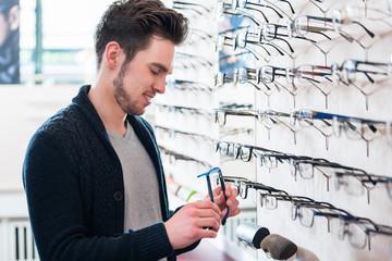 Mann als Kunde sucht Brille beim Optiker im Regal aus