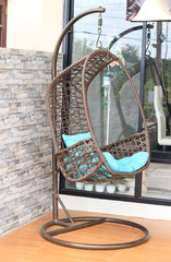 Wicker hanging chair swing hanging on a chain