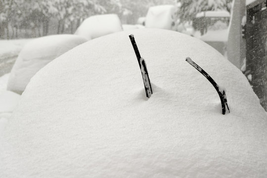 Car is fully covered with snow and lifted windshield wiper up against freezing of the rubber
