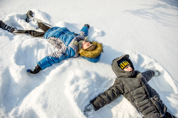 Two boys lying in the snow.