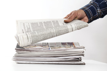 Man hand holding newspaper on table