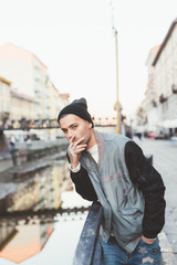 Young handsome tattooed caucasian man outdoor in the city smooking a cigarette - relaxing, bad habit concept