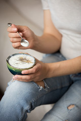 Closeup of woman's hands holding cup with organic yogurt with blueberries, coconut and fresh mint. Homemade vanilla yogurt in girl's hands. Breakfast, snack. Healthy eating and lifestyle concept.