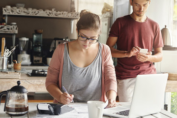 Young beautiful housewife wearing rectangular glasses making necessary calculations and writing down with pen, while paying utility bills, sitting at kitchen table with generic laptop and calculator