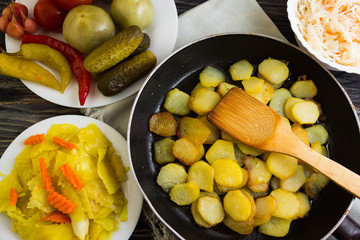 Fried potatoes in a pan with pickled vegetables