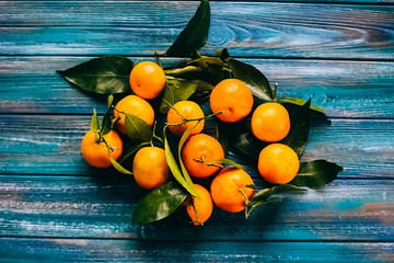 Tangerines with leaves on blue wooden table.