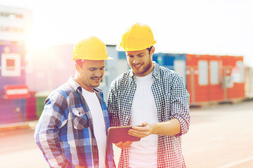 two smiling builders in hardhats with tablet pc