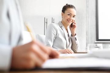 Obraz Doradca kredytowy. Bizneswoman rozmawia przez telefon siedząc przy biurku. - fototapety do salonu