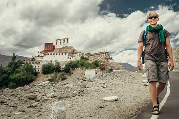 Young tourist man walks on road near Thiksey Monastery in India,