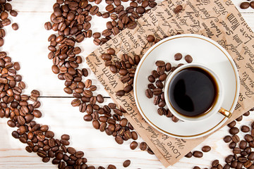 Cup of coffee, roasted coffee beans over on white wooden table