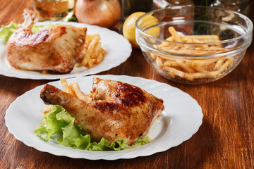 Roasted chicken legs with french fries and lettuce