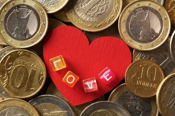 Red heart surrounded by various coins