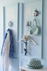 blue wall interior and clothes hangers with hat