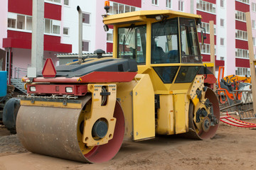 Large roller at construction site next to new building at summer