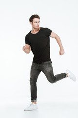 Attractive young man running over white background