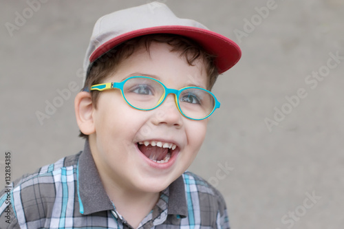 2620f33f53fc Little smiling boy in glasses and cap looks up outdoor, closeup ...