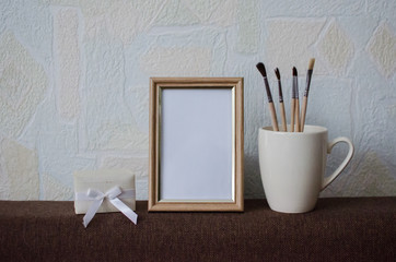 Empty photo frame and brush in pastel colors
