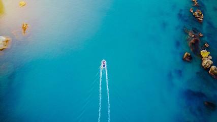 Boot aus der Luft/Schiff fährt neben Felsen Fototapete