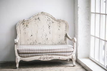 White textile classical style sofa in vintage room. White old ba