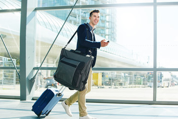 man walking with luggage and phone in station smiling