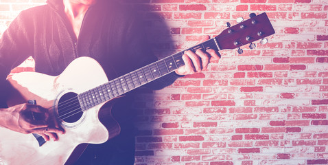 A man playing guitar on brick wall with croped image