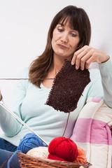 femme mécontente qui a des difficultés pour tricoter un pull