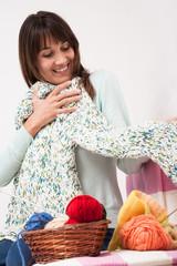 femme souriant qui tricote un gros pull en laine