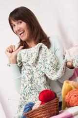 femme heureuse et fière souriant qui tricote un gros pull en laine