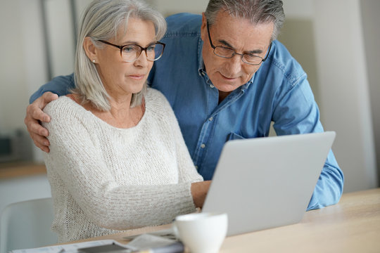 Senior couple at home using laptop computer