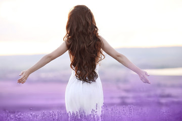 Free brunette woman with open arms enjoying sunset in lavender f