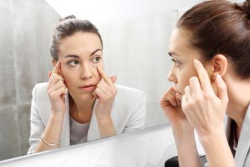 Obraz Odbicie w lustrze. Kobieta przegląda się w lustrze dostrzegając pierwsze zmarszczki  - fototapety do salonu
