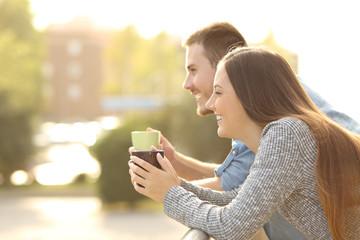 Happy couple enjoying breakfast in a balcony