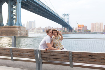 Young Beautiful Couple Taking a Picture of Themselves in Brooklyn Bridge . New York City