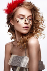 Beautiful girl in a gold dress with a gentle make-up. Model with red feathers on her head and curls. Holiday photo. The beauty of the face. The photo was taken in a studio.