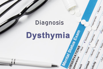 Diagnosis of Dysthymia. Results of mental status exam, container with crumbled pill with inscription psychiatric diagnosis Dysthymia on white background or white workplace psychiatrist or psychologist