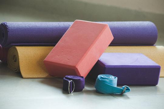 closeup of yoga blocks belts and mat props