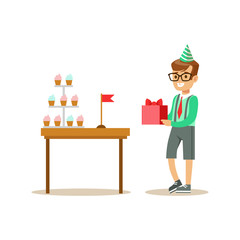 Boy Holding A Present Standing Next To Table With Cupcakes, Kids Birthday Party Scene With Cartoon Smiling Character