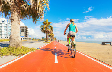 Girl on bike ridding on special bicycle lane on the sea coastline.