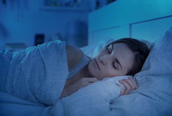 Girl peacefully sleeping in bed at night